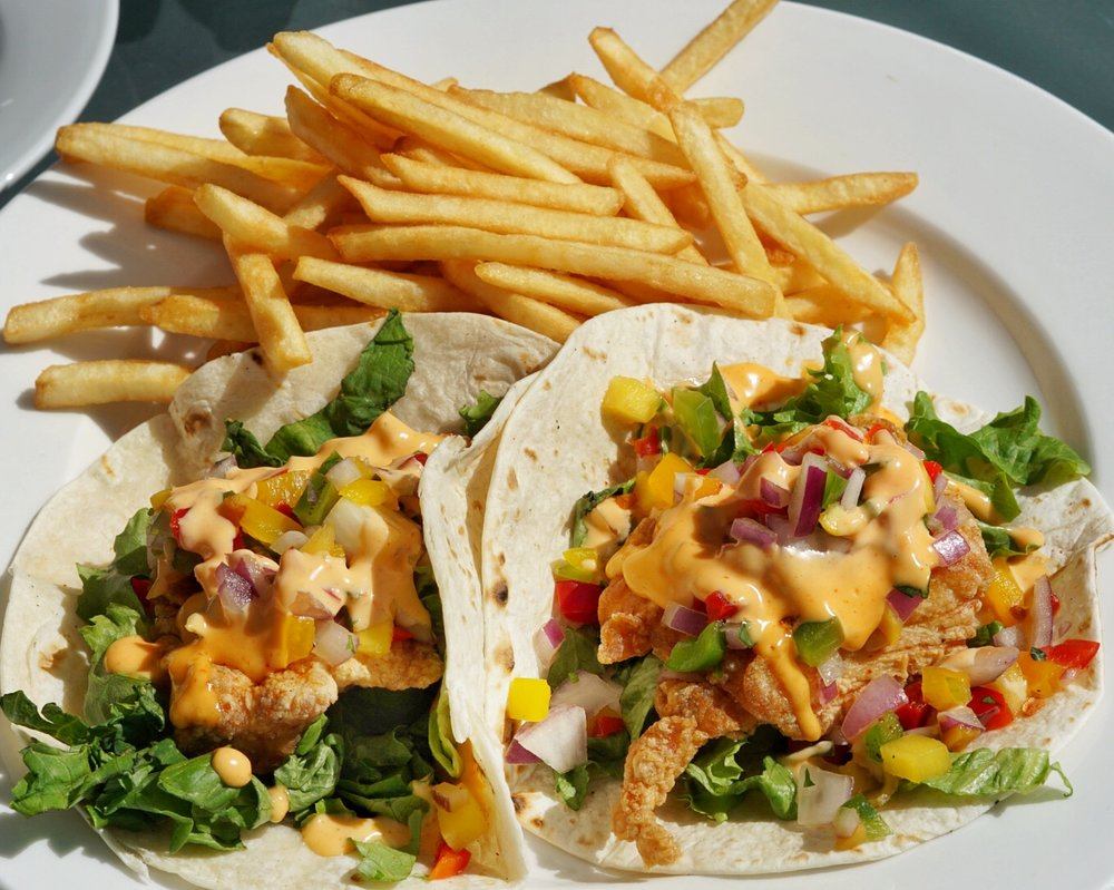 The famous Fish Tacos: Lightly battered snapper fillets with mango salsa, lettuce and spicy mayo in flour tortilla wraps and a side of fries.