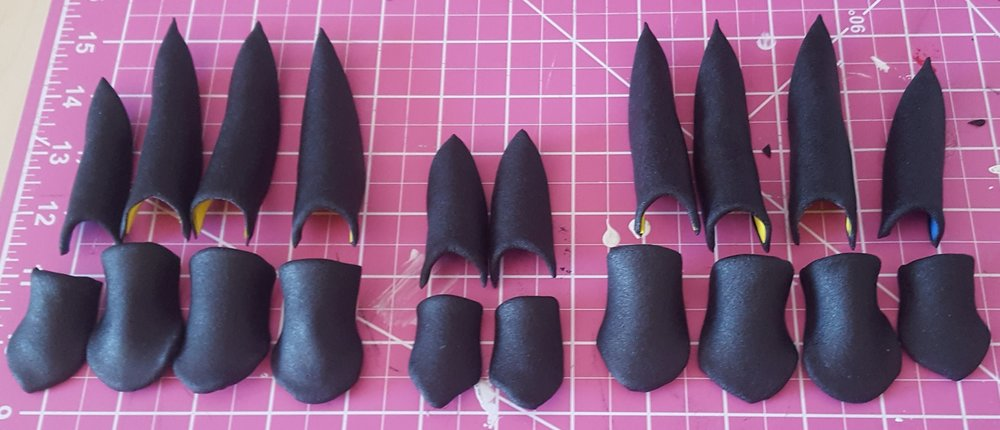 Each of the claw pieces for my gloves. You can see the craft foam underneath the black worbla, and the shape after I heat-formed them to each of my fingers.