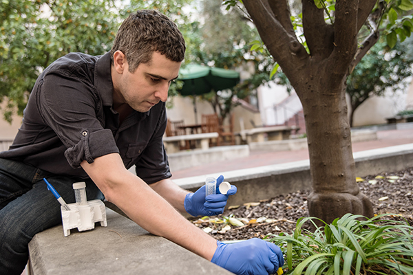 Kyle Costa, a postdoctoral scholar, collecting soil in the courtyard of Beckman Institute from which Dianne Newman's lab isolated a bacterium that disrupts biofilms.