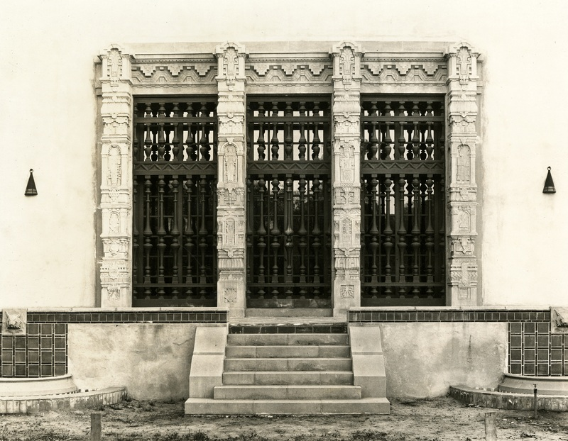 Windows of the Gates Annex library, with columns featuring Mayan Revival reliefs of animals and people.