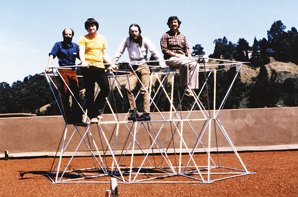 Jerry Nelson (far right) and friends appear atop a full·sized prototype of the supporting frame for a mirror segment.