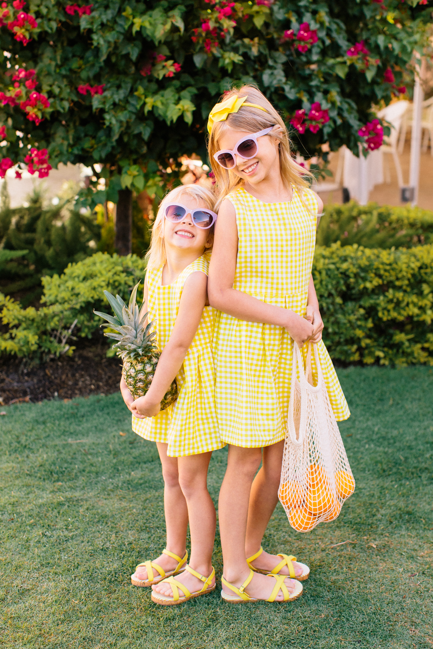 "Gingham Girls  - ""The gingham dress for little girls has a fitted top, full skirt and bow on the back neckline. My girls love the cheery yellow color and look like little rays of sunshine in them!""-Danielle Elsa and Emery in the"