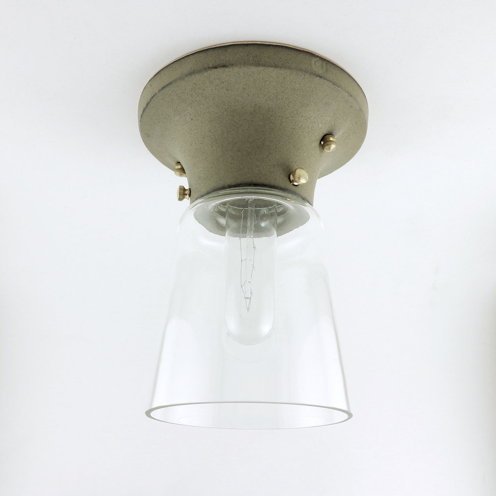 """No. 541 - The profile of the No. 541 rises in a continuous cove to a zone of three set screws which hold a conical glass shade. A milk glass shade will be available as well. The base diameter measures 5.5""""."""