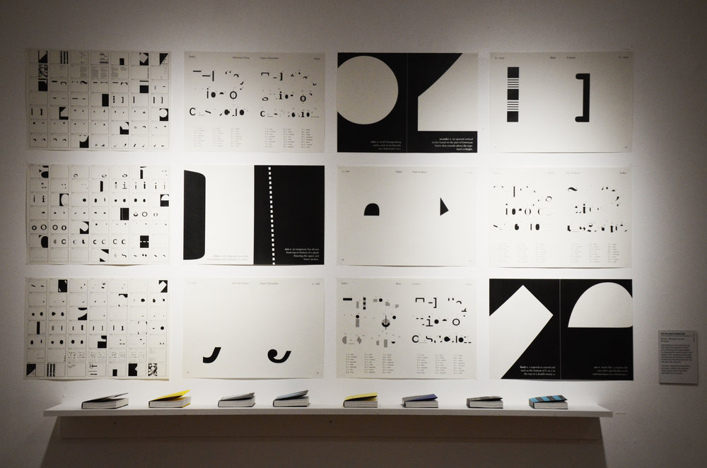 Display of book pages designed by everyone in the typography class, as well as the book covers on display below.