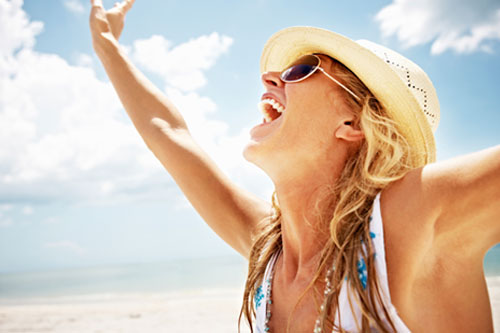 Happy middle aged woman on a Santa Barbara beach with arms up has smooth skin and perfect teeth.