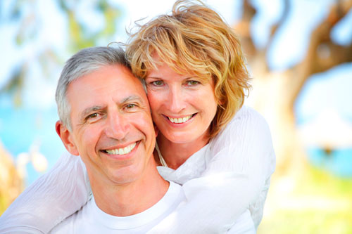 Middle Aged couple   with   dentures smiling from their yard on the edge of a Santa Barbara Beach.