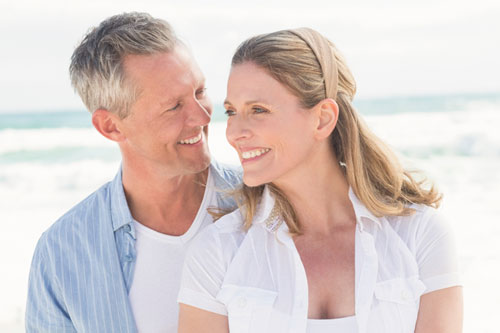 Middle aged couple on the Santa Barbara beach smiling with nice healthy teeth.