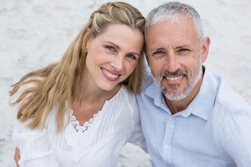 Middle aged couple sitting on a Santa Barbara Beach in the sand smiling up with healthy teeth.