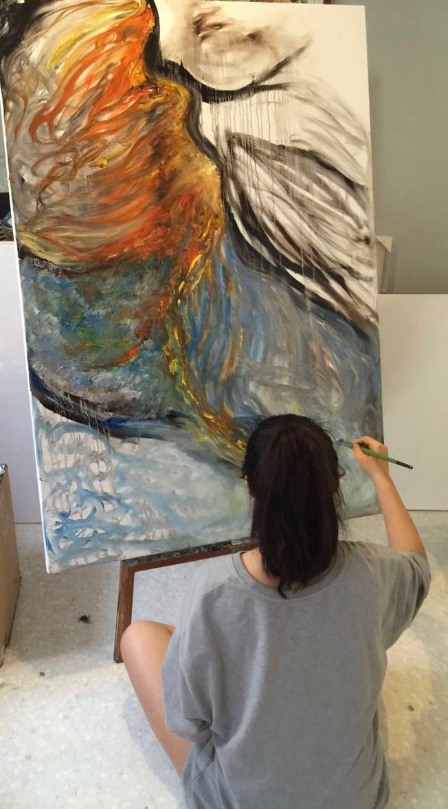 Emily works on her most recent painting, a piece she says focuses on identity.