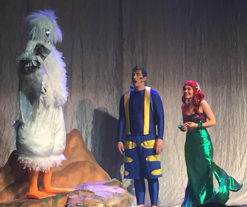 Junior Jude Ampfer (Scuttle), Senior Ali Doepker (Ariel), and Freshman Jack Greene (Flounder), shown in one of the ALL amazing scenes of Disney THE LITTLE MERMAID Production.  Congratulations to the cast and crew and all who had a part in making the spring performance a huge success!