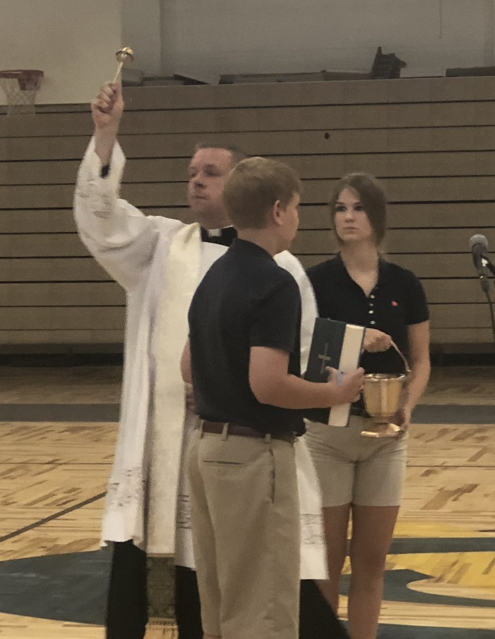 Fr. Britton Hennessey, Chaplain blesses the new gymnasium floor.