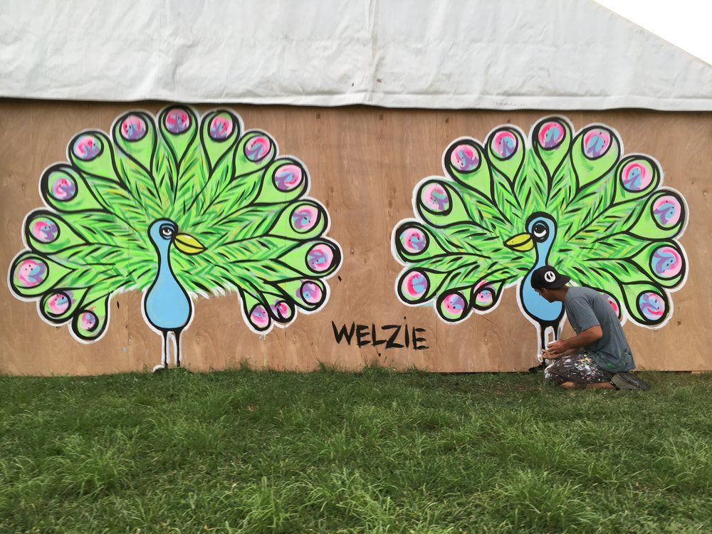 Two Heads are better than one. This image was taken at the 2016 Haleiwa Arts Festival. Since the wall was long and not that tall we went with 2 peacocks to cover the space. It worked out great for people to take pictures in front of.