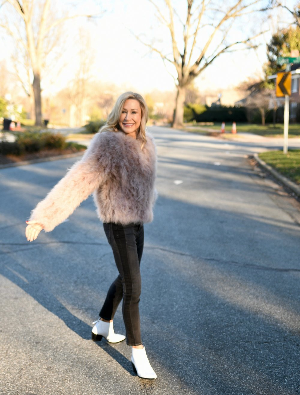 Pink fur coat with black jeans and cowboy booties