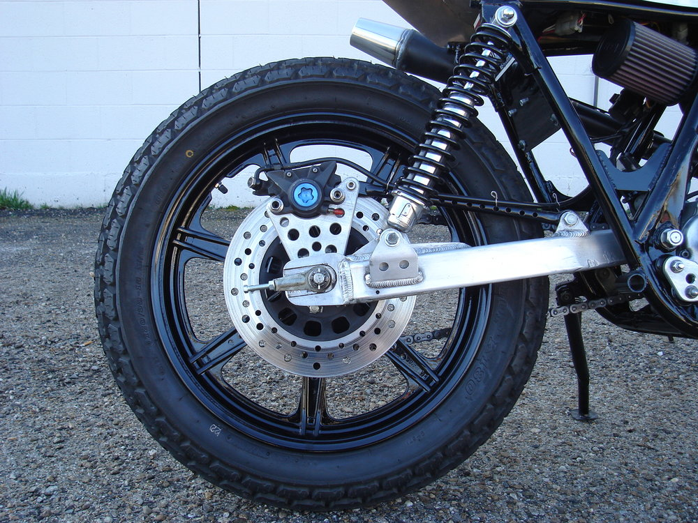 HAND DRILLED BRAKE ROTORS, CUSTOM BRAKE BRACKET, R-1 REAR CALIPER, ALUMINUM SWINGARM.
