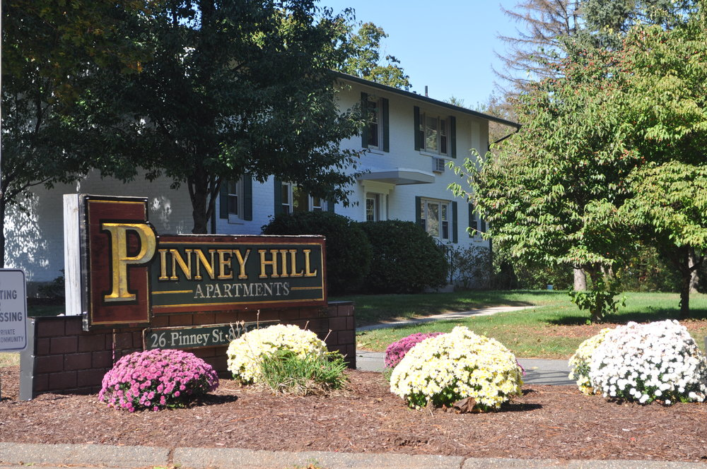 Pinney Hill Apartments property sign on an angle with pink and yellow flowers and Pinney Hill white and green building in background with trees.