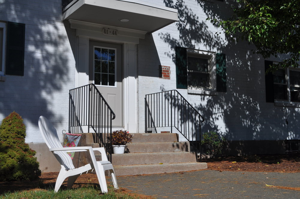 Front steps of a white building with a Adirondack chair with a shadow of the sun poking through the trees.