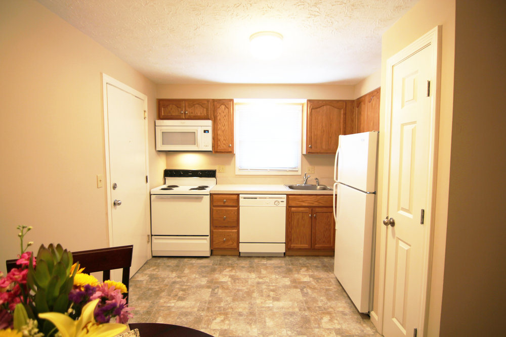 Image of a kitchen with a door to the left, microwave over a stove, cabinets, a window over a sink and dishwasher, more cabinets, a fridge and door to a pantry. Tile Floor and a small table on the bottom left.