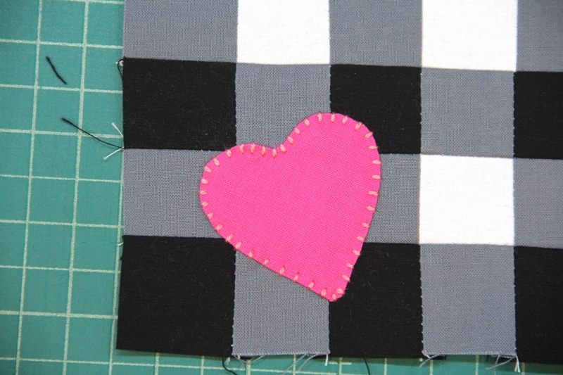 Stitch heart onto mat