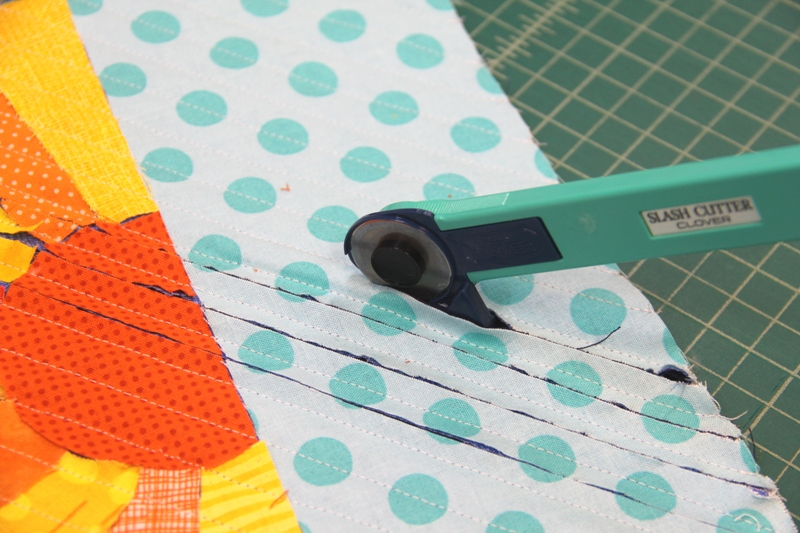 Use cutting tool to cut between stitching