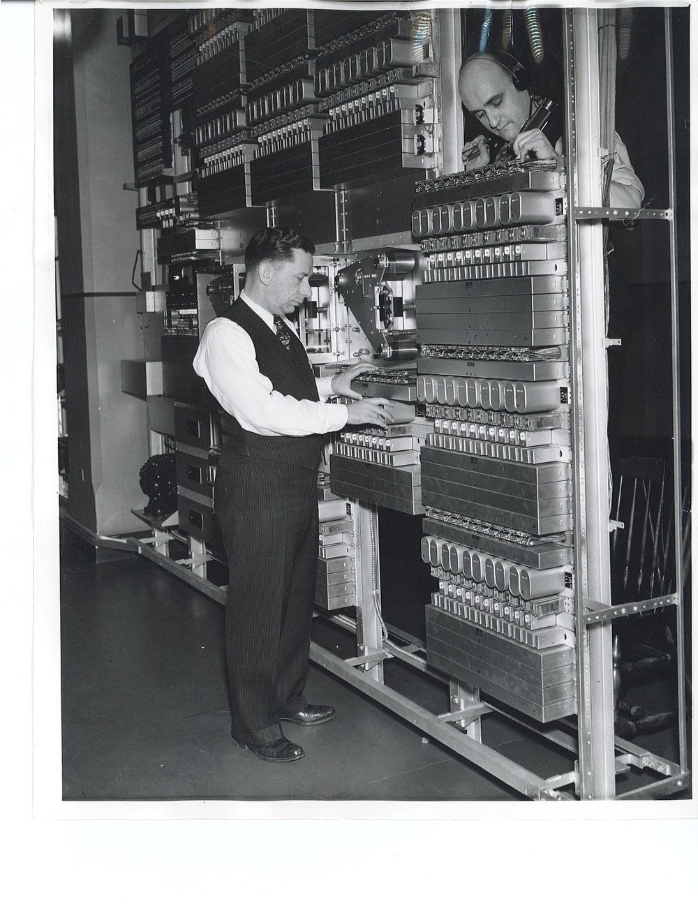 Maintenance men work on the automated recording and reproducing apparatus that communicated weather forecasts to tens of thousands of Detroit telephone users in 1940.