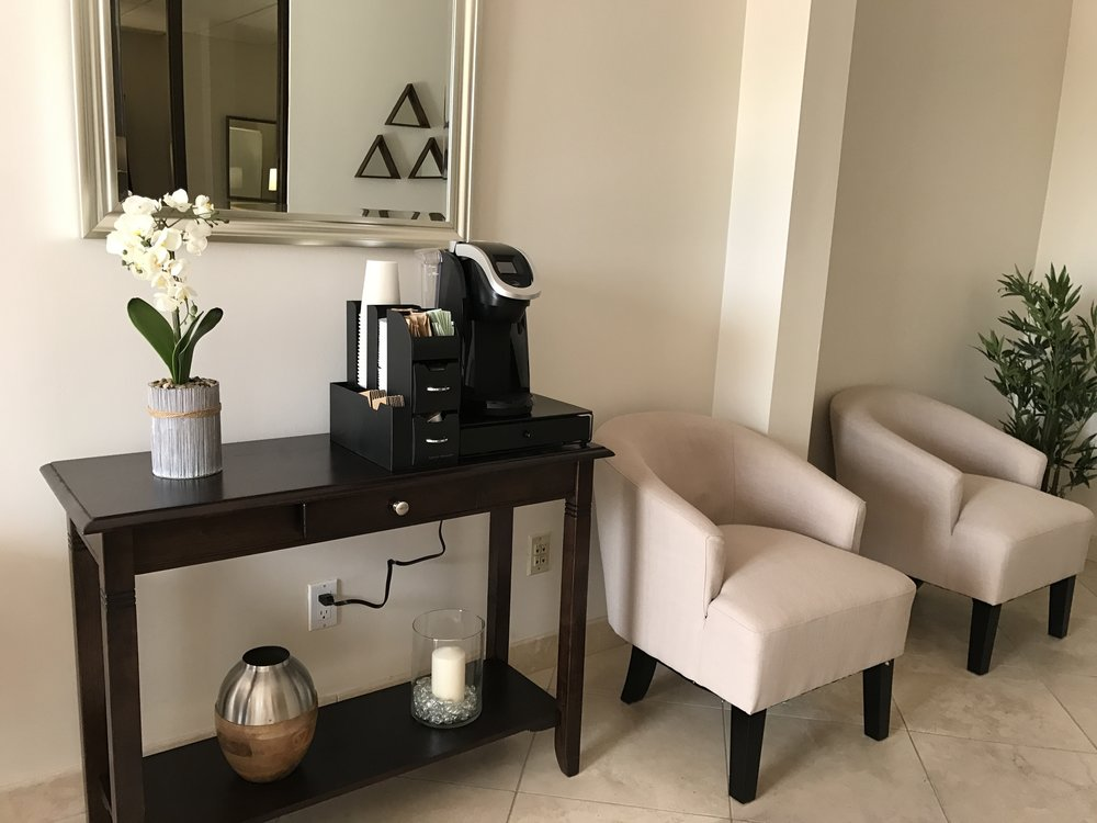 Office waiting room with chairs and coffee maker