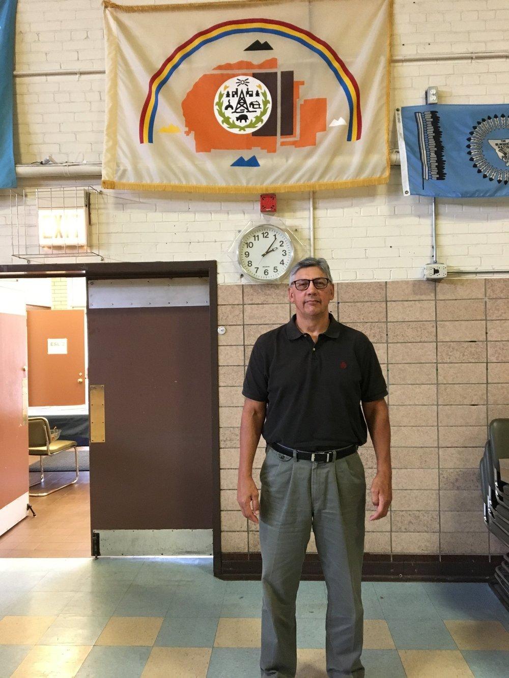 Les Begay beneath the Diné (Navajo) flag