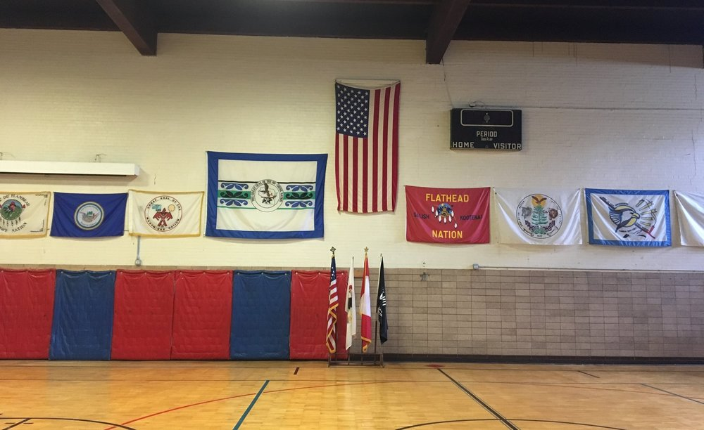 Community members' tribal nations' flags line the new AIC gymnasium.