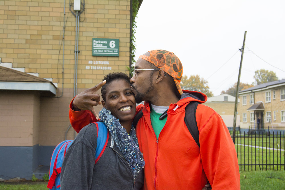 """We've been together for 16 years. We started up here. We met up here. I was fresh out of the penitentiary. We done moved outta here, came back here, and moved outta here. My mama live up here, now. This is us. We're in a battle, right now.  We've been railroaded by CPS. We gotta go to WHAS, this week. They're doing a story on us. I got Christopher 2X in my corner. I done talked to him for about an hour on my phone. We just went to court yesterday. We gotta go take a pee test today. They got us doing the drug screens. We've been clean for eight months.  We just now getting back, you know. We've been in this struggle together. You know what I mean? We done went through the bad and we've been through the good, but this is a reflection of our former self. It's like looking in the mirror. When we got up and used to look in the mirror, we've seen addicts and alcoholics. We don't see that, now. We see us.  Now, we're getting up and we're trudging. We're out here in the rain to go take a pee test. We just got our house. Everything is coming full circle, now. So the fact that you are out here taking a picture of us, is almost surreal. What you're seeing now, is almost due for a picture. You see what I'm saying? We've been through the storm. This is Pick Life. When you take the picture, use #PickLife. That's our motto. We got 9 kids and all of our kids have Pick Life. Two of my children got it tattooed on them. I'm very proud of that because back in the day, in Africa, that's what they did to represent their tribes. They would put their tribal name on them. Ours is Pick Life because our last name is Picken and we pick life over death. That's our choice. You know what I mean? We pick life. Hashtag Pick Life!  Plus, she's a cancer survivor, so our story is big. This picture is probably gonna make you famous because we're taking it to the top. God makes no mistakes."" - James & LaShonda, Park Hill"