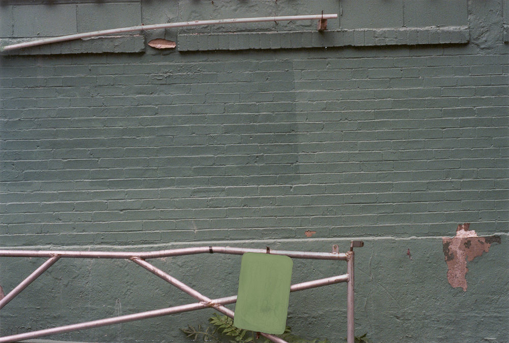 Erasure (green sign green wall metal fence)