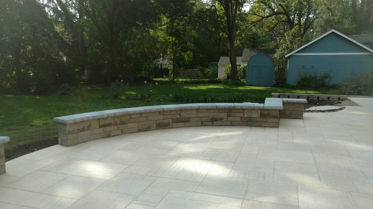 Patio-redesign - Libertyville, IL Believe it or not this particular patio have man made slabs as the patio surface.  The ivory color Travertina from techno-bloc made the large surface area look less busy with longer joint lines.