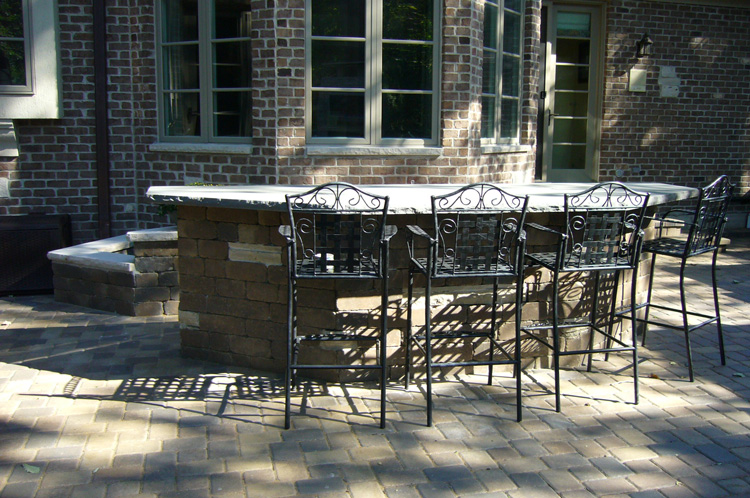 Outdoor living -  Simple but spacious outdoor tabletop used for serving and seating. A mix of man made stone and natural accent pieces this tabletop and matching planter box is subtle but bold