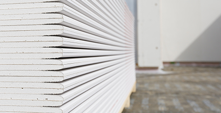 stock-photo-stack-of-plasterboard-panels-at-construction-site-206717068.jpg