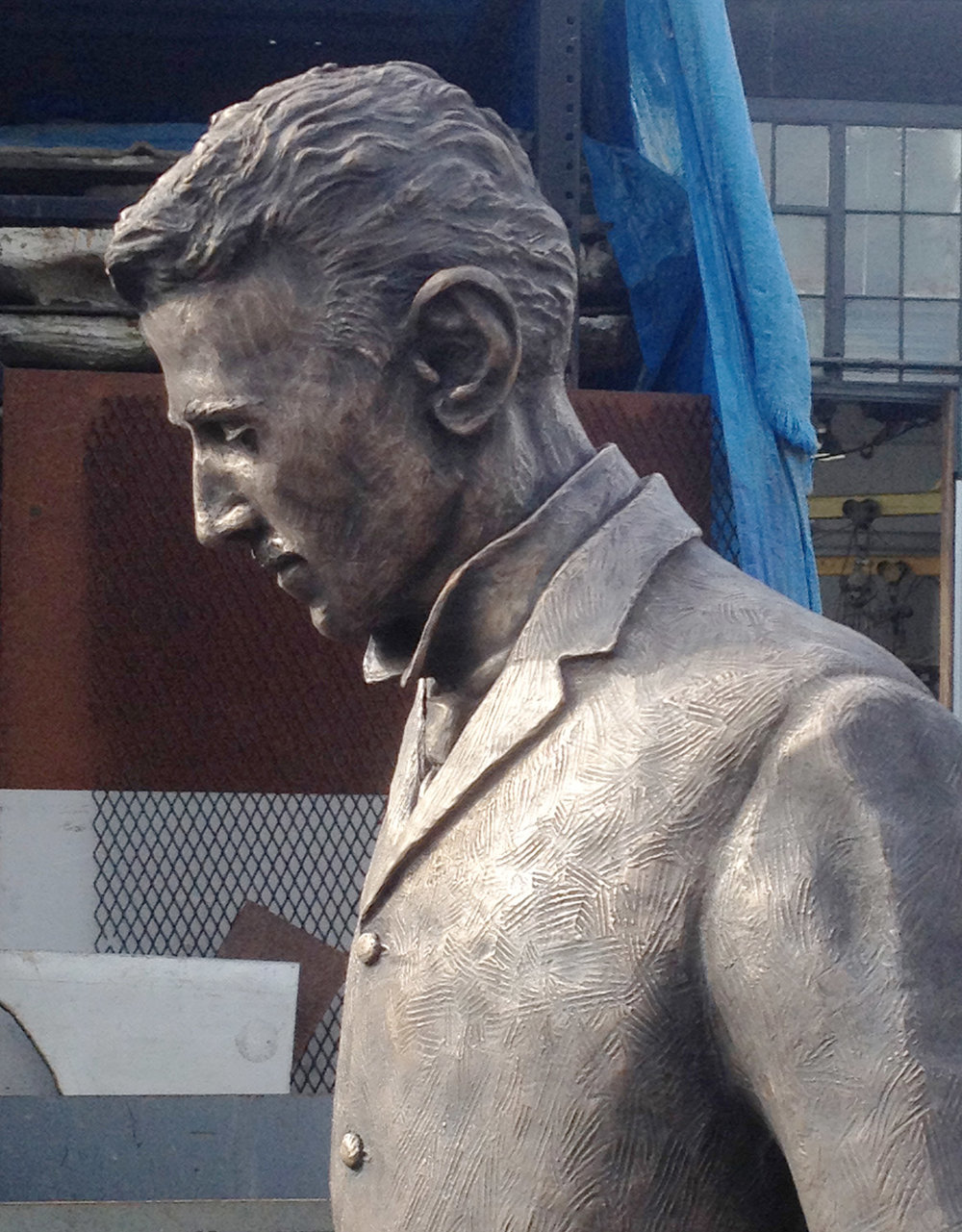 Detail of of the Nikola Tesla statue head and shoulders during patina process at Artworks Foundry in Berkeley California.