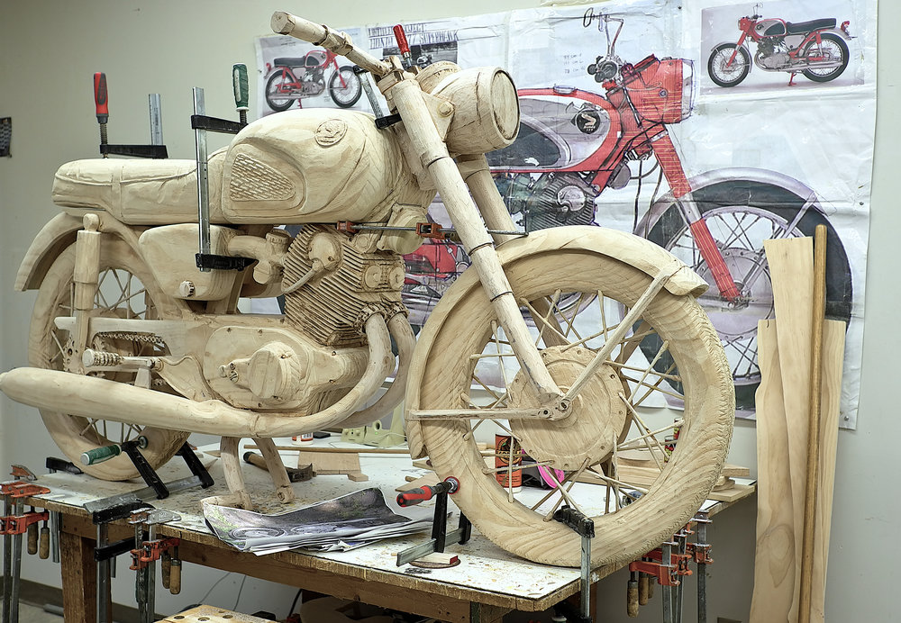 A carved/painted sculpture of a 1964 Honda CB77 Superhawk motorcycle at 1:1 scale. The Honda CB77 Superhawk is known for its speed, power and reliability and in many ways set the paradigm for modern motorcycles. This particular motorcycle also has a specific literary connection––to the 1970's best selling novel Zen and the Art of Motorcycle Maintenance.  A significant part of this project is embedded in its conflation of construction-as-maintenance as part of a dialectical motion, connecting labor to material to economies—a complex gathering of a self in the world.