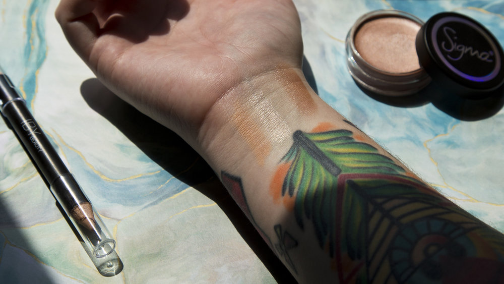 In direct sunlight and a little underexposed so you can see the shimmer better: IBY Beauty Dual Brow Highlighter on the left and Sigma Beauty Shimmer Cream in Brilliant on the right (click to enlarge).