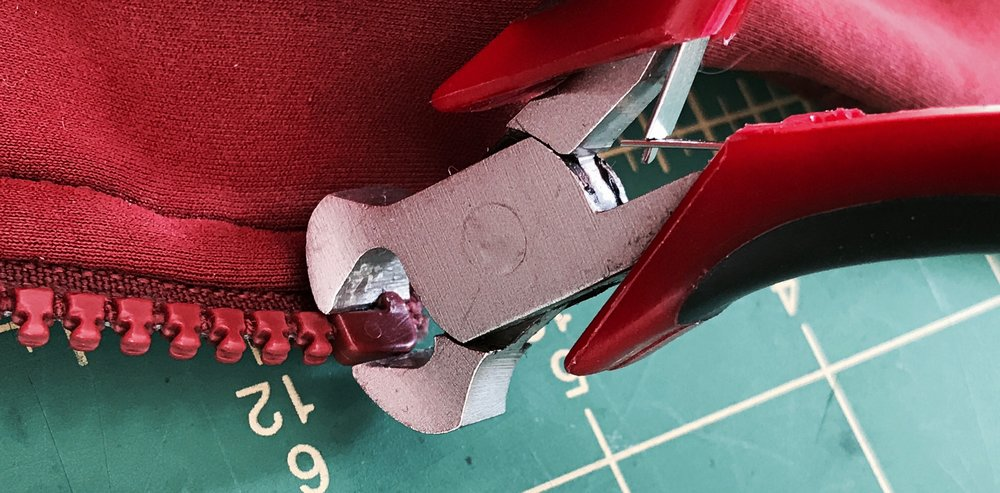 Cutting the factory top stop off the slider side of the zipper. once removed, the old slider slides off and the new one can go right on in it's place.