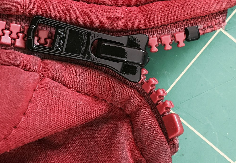 The replacement zipper slider and top stop in place.