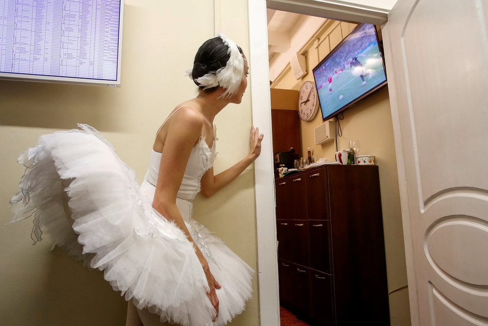 A ballerina watches the World Cup quarter-final match between Russia and Croatia at the Mikhailovsky Theatre in Saint Petersburg, Russia. Photo by Anton Vaganov.