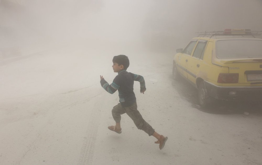 A boy runs after airstrikes conducted by Syrian government forces hit a neighborhood in rebel-held Aleppo on April 24, 2016. Photo by Beha el Halebi.