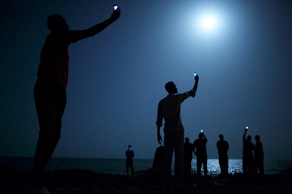 African migrants on the shore of Djibouti City at night raise their phones in an attempt to catch an inexpensive signal from neighboring Somalia—a tenuous link to relatives abroad. Photo by John-Stanmeyer.