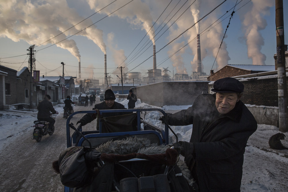 Clouds of smoke and steam billow from chimney stacks as a man pulls a trolley through a neighbourhood next to a coal fired power plant in Shanxi, China.  Photo by Kevin Frayer.