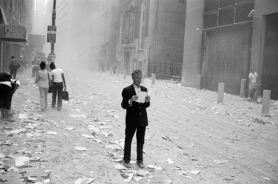 9/11/2001. A dazed man picks up a paper that was blown out of the towers after the attack of the World Trade Center, and begins to read it. Photo by Larry Towell.