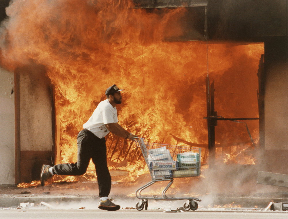 A man rushes off with a shopping cart full of diapers. The acquittal of four police officers whose assault on black motorist Rodney King was watched on TV by millions, sparked off mass looting and rioting. The disturbances claimed 58 lives and many buildings were destroyed by fire. Photo by Kirk McKoy.