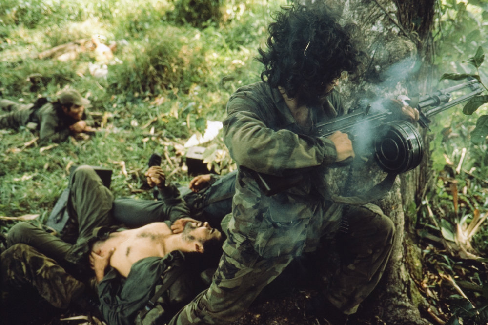 A Contra fighter shoots at government forces while his friend lays dying. Photo by James Nachtwey.