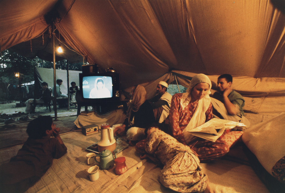 Farani family watch Pakistani TV in their tent in a refugee camp outside Peshawar, Pakistan. Photo by Steve McCurry.