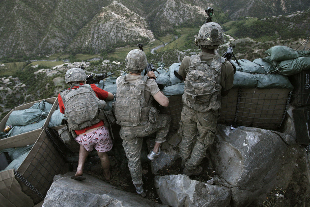 US soldiers take defensive positions after receiving fire from the Taliban in Korengal Valley, Afghanistan on 11 May. Specialist Zachery Boyd was wearing 'I Love NY' boxer shorts when he rushed from his bunker to support fellow platoon members. Photo by David Guttenfelde.