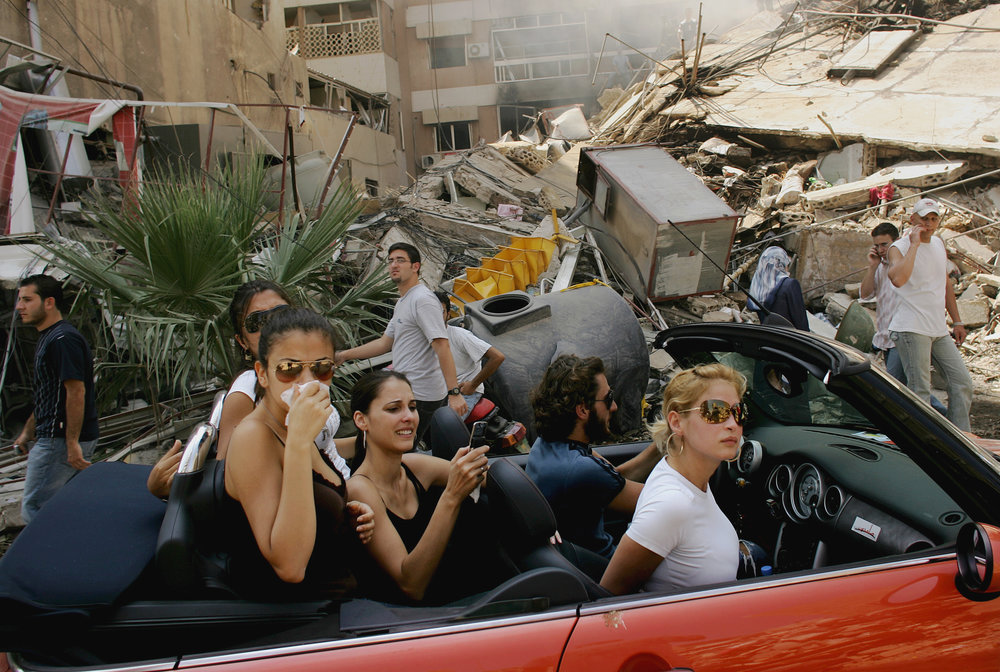 Beirut, Lebanon. Young Lebanese drive down a street in Haret Shreik, a southern suburb of Beirut, to check on their homes after bombardments by Israel. For nearly five weeks in 2006, Israel had been targeting that part of the city and towns across southern Lebanon in a campaign against Hezbollah militants. Photo by Spencer Platt.