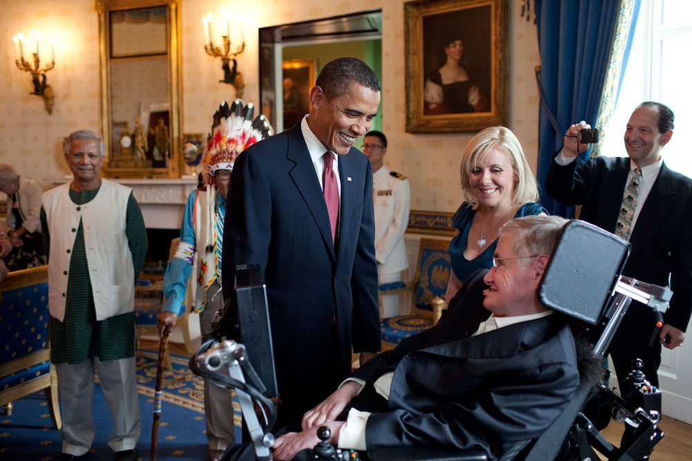 United States President Barack Obama talks with Stephen Hawking in the Blue Room of the White House before a ceremony presenting him and 15 others the Presidential Medal of Freedom on 12 August 2009. The Medal of Freedom is America's highest civilian honor. To Stephen's right is his daughter Lucy Hawking and on the left of the image is Muhammed Yunus, who received the same award.