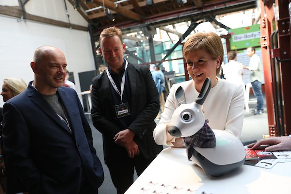 From left to right:  Pat Kane  (from A/UK), Geoff Mulgan, CEO of Nesta, and First Minister Nicola Sturgeon. Also MiRo, the robot rabbit-dog.