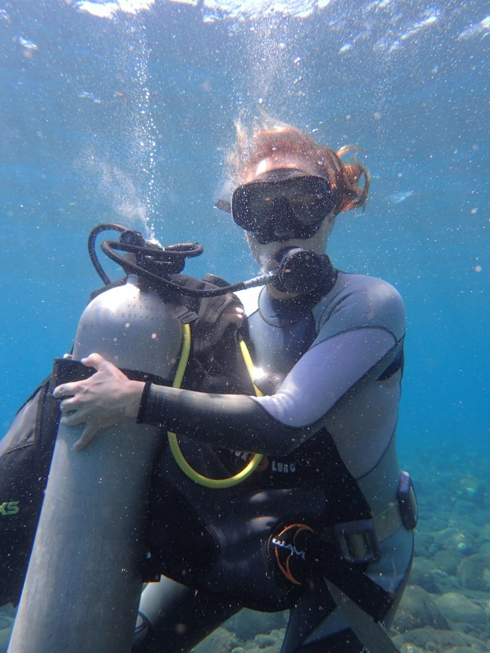 Practicing removing and putting on tank under water on first dive